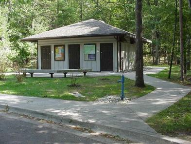 PLATTE RIVER CAMPGROUNDFront of comfort station showing sidewalk leading up to building, two benches, and water spigot