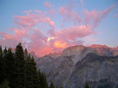 Sierra Nevada Wilderness Mountains with conifers and clouds at sunset.