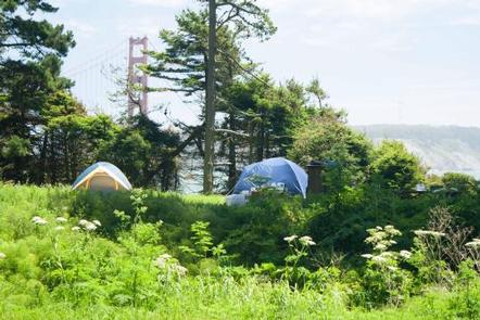 Tents within a green field, with a view of the Golden Gate BridgeCatch a stunning view of the Golden Gate Bridge on clear days!
