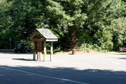 Paved entry with kiosk and fee tube in front of parking area and large evergreen shrub tree.TAHKENITCH CAMPGROUND