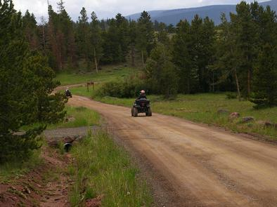 Individual riding an ATV on a dirt road.Browne Lake Area