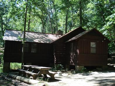 American chestnut log cabin #16 with two picnic tables and outdoor grill/firepit surrounded by trees.American chestnut log cabin #16 with two picnic tables and outdoor grill/firepit surrounded by trees. Cabin #16 has electricity, a full bathroom, small refrigerator, microwave and heat.  The cabin can accommodate 6 individuals.