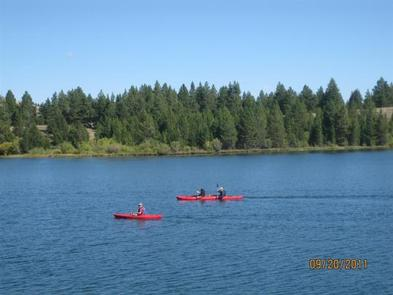 Kayakers on Hebgen Lake with pine trees in backgroundHebgen Lake