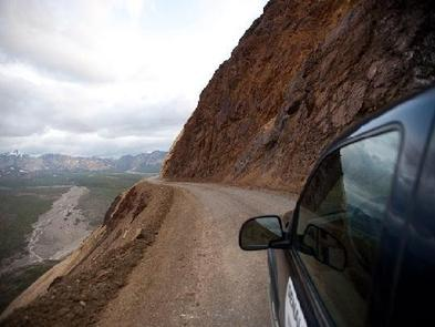 A car driving on a dirt road carved into the side of a cliff with a steep drop off on the left side.DENALI NATIONAL PARK - ROAD LOTTERY