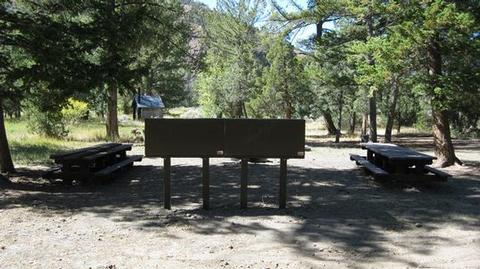 CLEARWATER CAMPGROUND OVERVIEWSign with picnic tables and restroom in the background