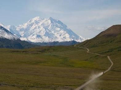 A view of a  a dirt road crossing a green valley with Denali towering in the distanceDENALI NATIONAL PARK - ROAD LOTTERY