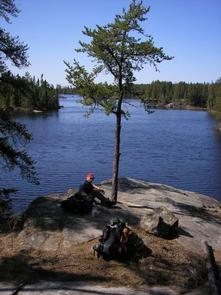 backpacker resting in BWCAWBackpacker resting on side of lake in BWCAW