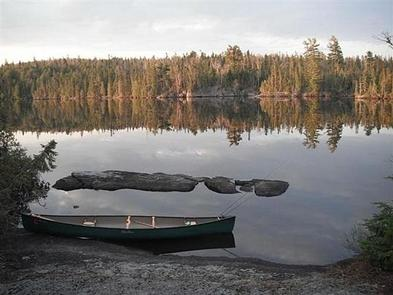BWCAW Canoe on side of lakeCanoe on side of still lake in BWCAW