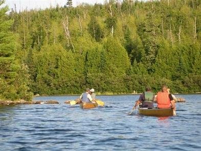 People canoeing in BWCAWbacks of people canoeing on lake in BWCAW