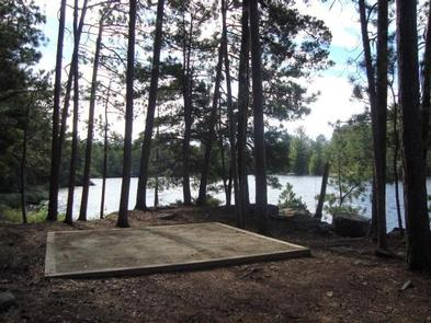 Square tent pad surrounded by trees and a scenic lake.Campsites have tent pads to stake out your tent on and get a good nights sleep.