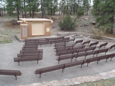 Amphitheater with brown benches and a tan building surrounded by pine treesThe Amphitheater located in Juniper Family Campground hosts interpretive programs presented by park rangers during the summer months. Check the Visitor Center for program schedule.