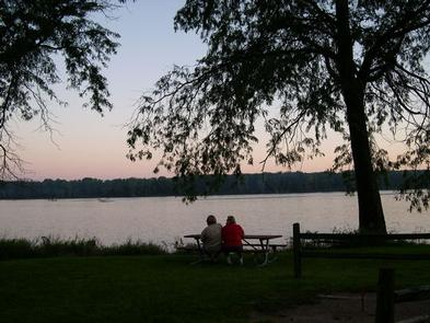 People at a picnic table at sunset overlooking the river.