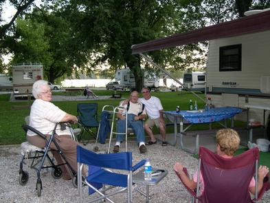 Senior campers using chair assistance and visiting at campsite.