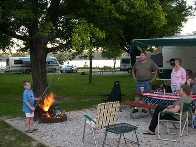 Young boy roasting marshmallows with adults watching at campsite.