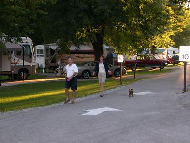 Campers walking their dog down the campground road.