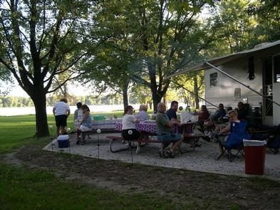 Large Group of people at campsite picnic tables.