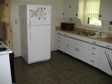 Kitchen with full size fridge with upper freezer, microwave next to metal sink with dish rack across from electric stove.kitchen