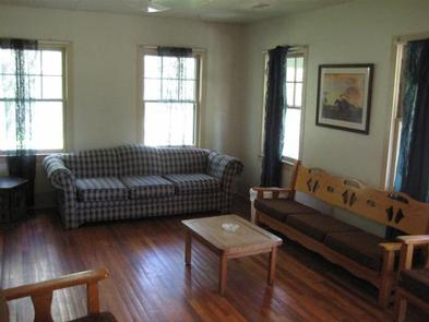 Cabin living room with couch, three person bench, coffee table and chairs.Living room