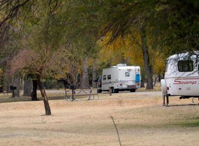 Two travel trailers in campsite with trees lining the sites and roadwayCottonwood Campground with travel trailers