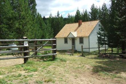 White cabin in meadow with rail fence and pine treesDITCH CREEK GUARD STATION CABIN