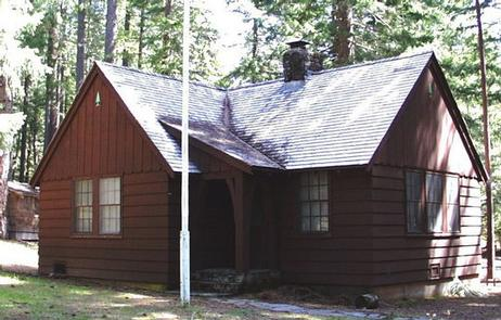 Flag pole in front of L-shaped house in conifer forest.IMNAHA GUARD STATION