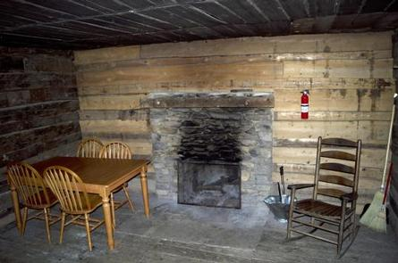 Fireplace, table and chairs, and rocking chair inside cabin