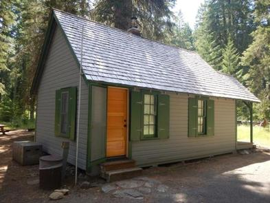 Gray cabin with three windows with green shutters and two steps up to  one wood door in front of a small lawn and conifer forest.BOX CANYON GUARD STATION CABIN