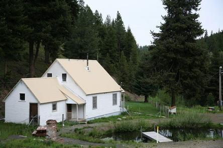 White house on flat green grass between a conifer covered hill and a small pond with a dock.CONGO GULCH