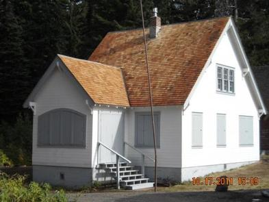 Sunlit white cabin with shutters closed, gray trim and six steps up.GODMAN GUARD STATION