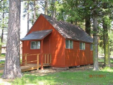 Small, orange-red cabin with ramp to front door in sun dappled conifer forest.SUMMIT GUARD STATION BUNKHOUSE