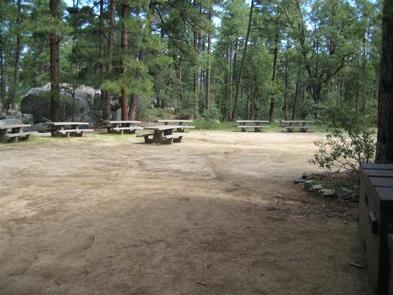 Picnic area with 8 tables in an open graveled space. House sized boulder in background with Ponderosa trees..GROOM CREEK SCHOOLHOUSE Picnic area