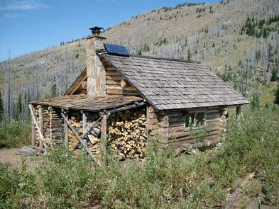 Log cabin with a full woodshed overlooking a hillside blanketed with silvered conifer snags.SNOW PEAK CABIN