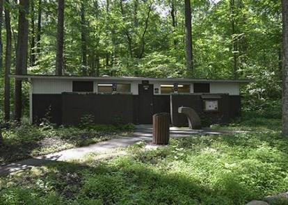 Front view of upper comfort station building showing 2 windows, door and paved path. Dense deciduous forest visible behind buildingOwens Creek Campground has 2 heated comfort stations with separate Men's and Women's facilities.  Amenities include flush toilets, sinks, mirrors and hand dryers.  The lower comfort station has hot showers.