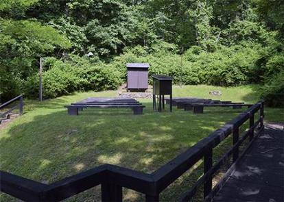 Campground amphitheater. Wooden boardwalk leading to open grass area with 10 wooden benches facing wooden projection screen.  Dense green vegetation is behind theater.Enjoy an evening program at the campground amphitheater.