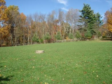 Large outside grass athletic field located behind the dining hall.  Trees showing fall foliage in the distance.The large grass athletic field located behind the dining hall is great for a variety of activities!