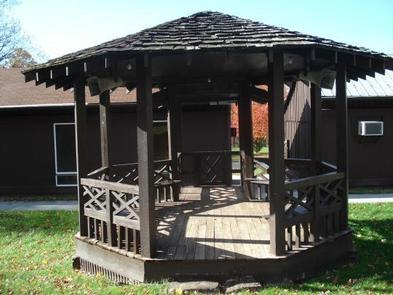 Small 9 foot wooden gazebo is located outside near the front door of the dining hall.