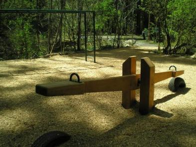 Wood chip covered play ground with wooden see saw and monkey bars next to tree lined roadway.RUJADA CAMPGROUND