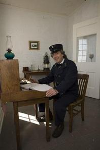 A man dressed as a lighthouse keeper sits at a desk.Historic Yaquina Head Lighthouse tours.
