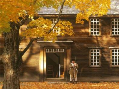 Minute Man National Historical Park ToursAn armed minute man stands in front of Hartwell Tavern on an autumn afternoon