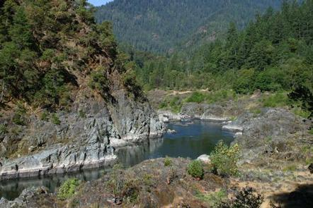 A bend in the Rogue River rounds a rocky cliffside, bordered by forest.