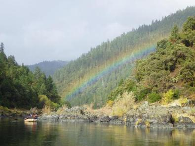 A raft floats by as rainbow crosses a tree-lined canyon on the Rogue Wild & Scenic River.A rainbow on the Rogue.
