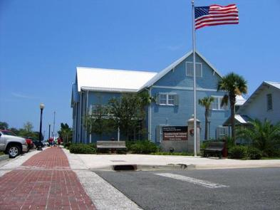 two story blue building along the waterfront with American flag flyingThe Mainland Visitor Center is the starting point for a visit to the island. Here you can find out information and check in the morning of your visit.