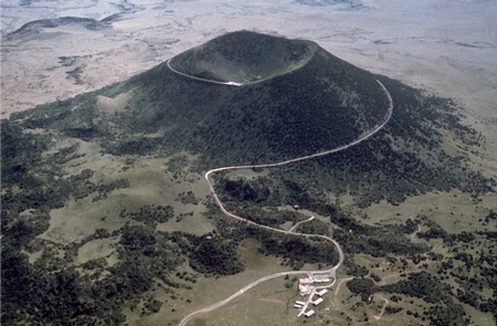 Aerial View of Capulin VolcanoCapulin Volcano is a classic example of a cinder cone. The crater is approximately 130 m (420 ft) deep and 440 m (1,450 ft) across. The base of the mountain is 6 km (4 mi) in circumference. Volcano Road spirals up the volcano, providing panoramic views.