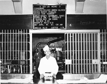 Serving the Christmas Meal, c 1951An inmate worker distributes trays near the steam table. Bars separate the kitchen from the mess hall.  The day's menu, the Christmas meal, appears on a sign over his head. The menu includes consomme, stuffed celery, green olives and mixed sweet pickles,