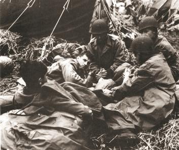 Challenging weather conditionsSoldiers rub the frostbitten feet of a disabled soldier. Over 2000 weather-related casualties—the majority Attu feet—were recorded for U.S. troops. This number represents the largest classification of casualties suffered by American forces on the island.
