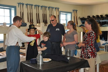 Visitors in the BarracksA volunteer shows visitors how soldiers lived during the 1860s at Fort Larned.
