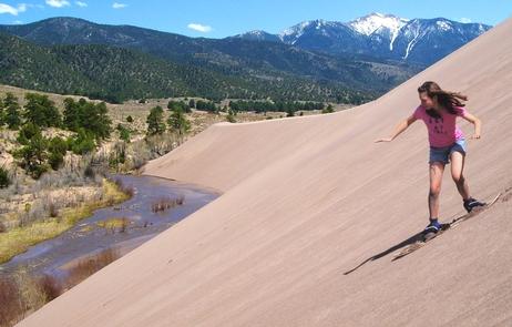 Girl Sandboarding Above Castle Creek Picnic AreaRent specially designed sandboards or sand sleds. Note: cardboard, snow sleds, saucers, etc. don't slide on dry sand.