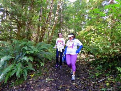 Running on HistoryRunners compete in a friendly race along a fern and tree-lined trail.