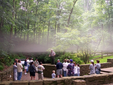 Fog at the Historic Entrance of Mammoth CaveA layer of mist hangs over a small tour group gathered at the Historic Entrance of Mammoth Cave on a summer day - it both delights the skin and fogs spectacles, and gives a sense that one is on the threshold of another world.