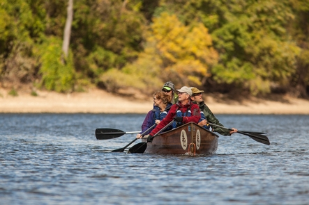 Modern day Voyageurs Paddle the Mississippi RiverA Voyageur canoe makes headway up a river while surrounded by autumnal color.